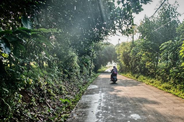 Dvaja ľudia idú na motorke po asfaltovej ceste medzi stromami a zeleňou.jpg