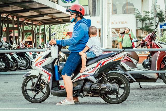 Muž s dieťaťom na motorke stojí uprostred rušnej ulice.jpg
