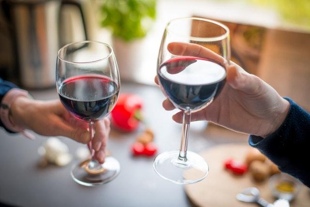 Dve osoby si štrngajú pohármi s červeným vínom.jpg
