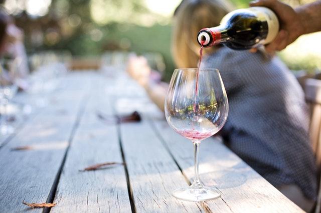 Človek nalieva víno do vysokého pohára položeného na drevenom stole.jpg