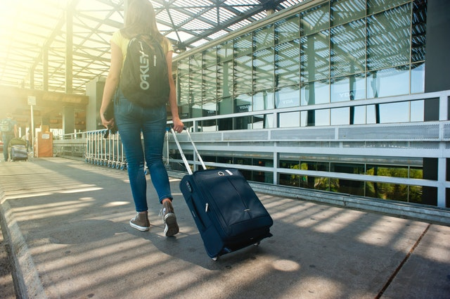 Dievča s kufrom na kolieskach kráča ku letisku.jpg