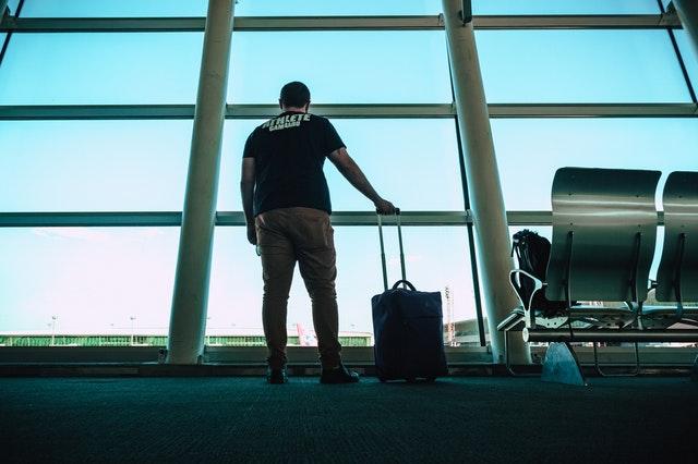 Muž s batožinou čaká v letiskovej hale pri okne.jpg