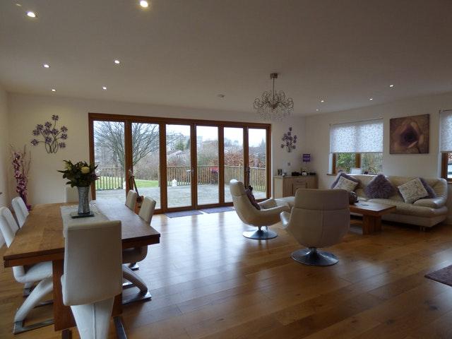 Veľká miestnosť s drevenými podlahami, nábytkom a sklenenými dverami do záhrady