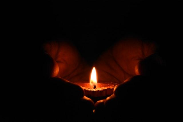 Človek drží v dlaniach zapálenú sviečku