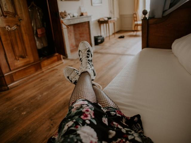 Žena v kvetovaných pančuchách a teniskách leží na posteli s bielou obliečkou