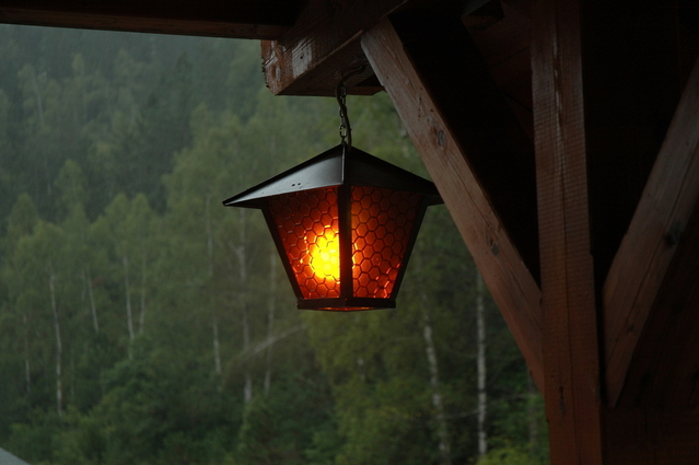 Lampa v tvare lampiónu zavesená na drevenej budove