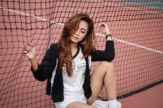Žena v bielom tričku s nápisom  sedí pri tenisovej sieti.jpg