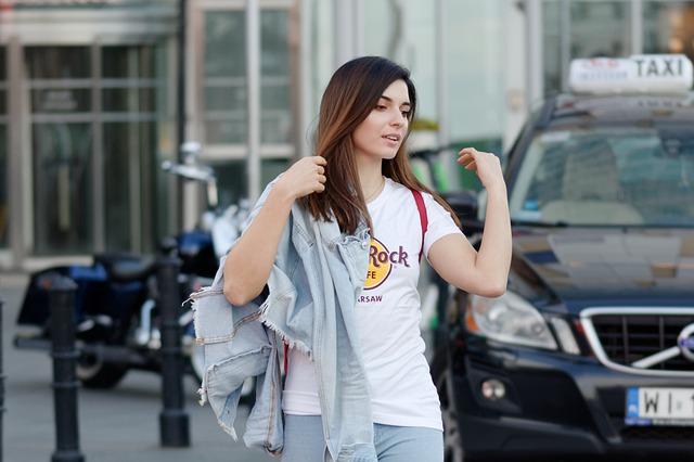 Žena v bielom tričku s nápisom a rifľovou nudnou v ruke ide po ulici.jpg