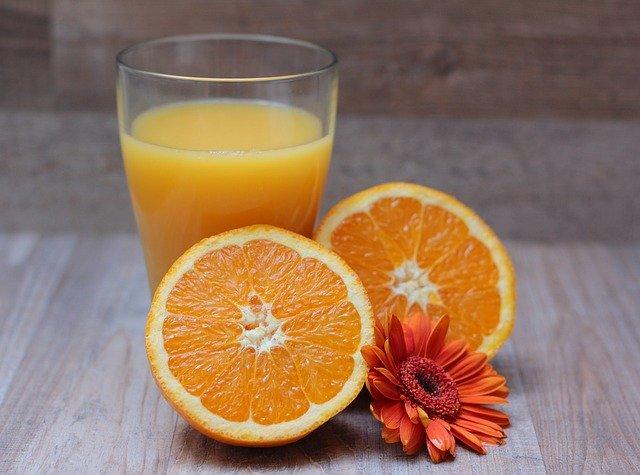 Pomarančová šťava v pohári a rozkrojený pomaranč