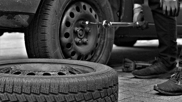Človek dáva z auta dole pneumatiky.jpg