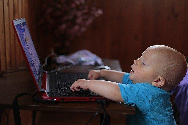 Bábätko píše na notebooku položenom na stole.jpg